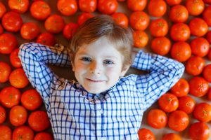 Adorable little kid boy with mandarin oranges background. Happy smiling child with lot of fruits. Healthy food, eating and lifestyle concept.